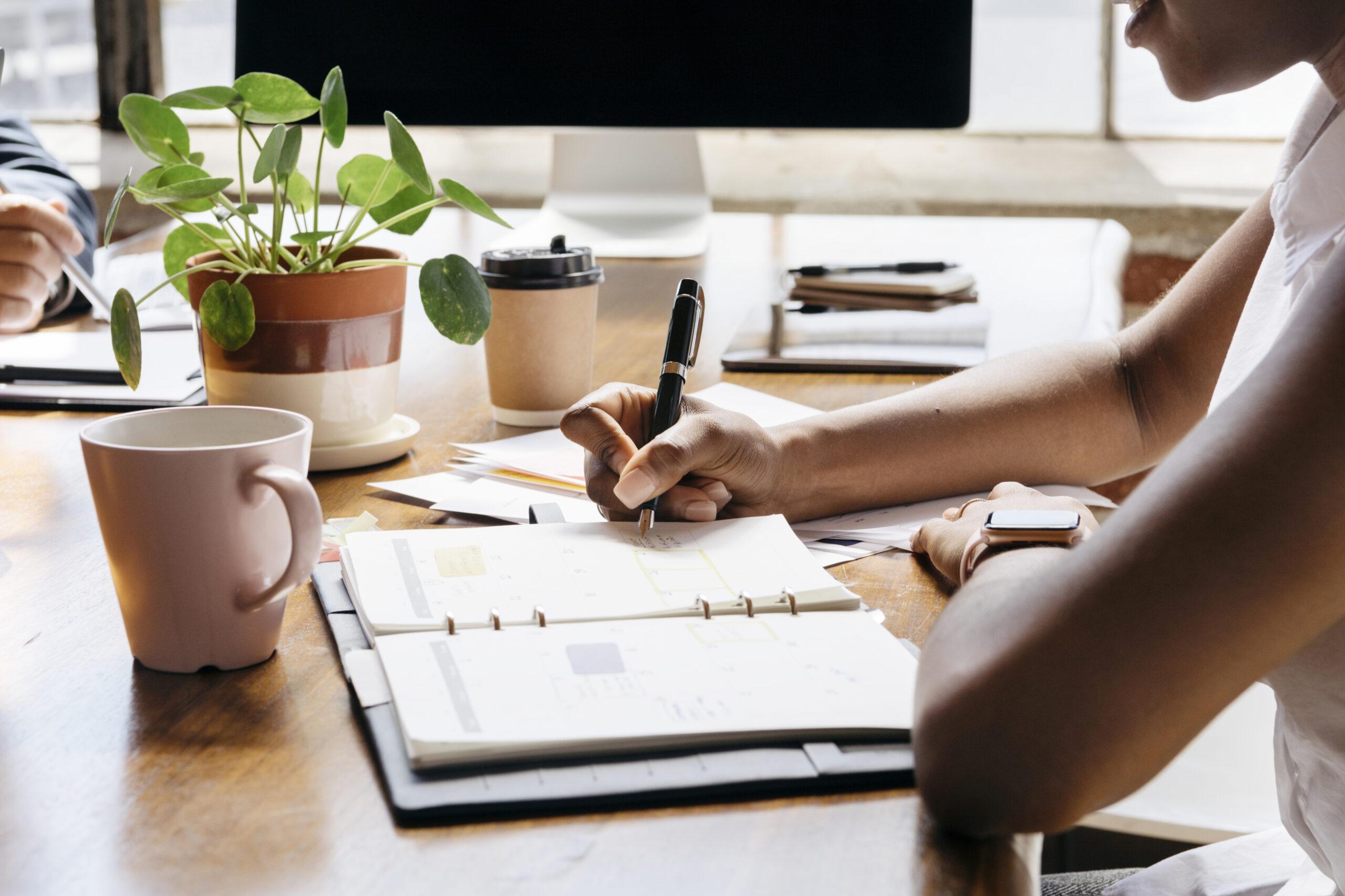 Businesswoman writing on personal organizer schedule